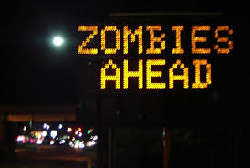 road sign that was hacked, now warning of zombies ahead.