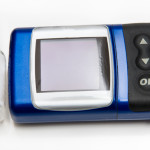 Bottle of insulin and small blue handheld insulin pump