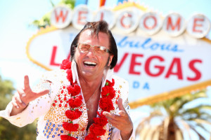 man dressed like Elvis in front of Welcome to Las Vegas sign
