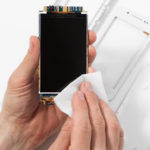 Repairman cleaning smartphone screen