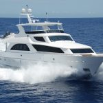 white luxury boat in the ocean with waves coming off the bow