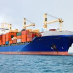 blue ship loaded with cargo containers in bright colors on ocean