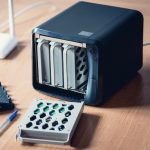 small black 4-bay NAS hard drive enclouse with face open and one empty bay laying on wood desktop
